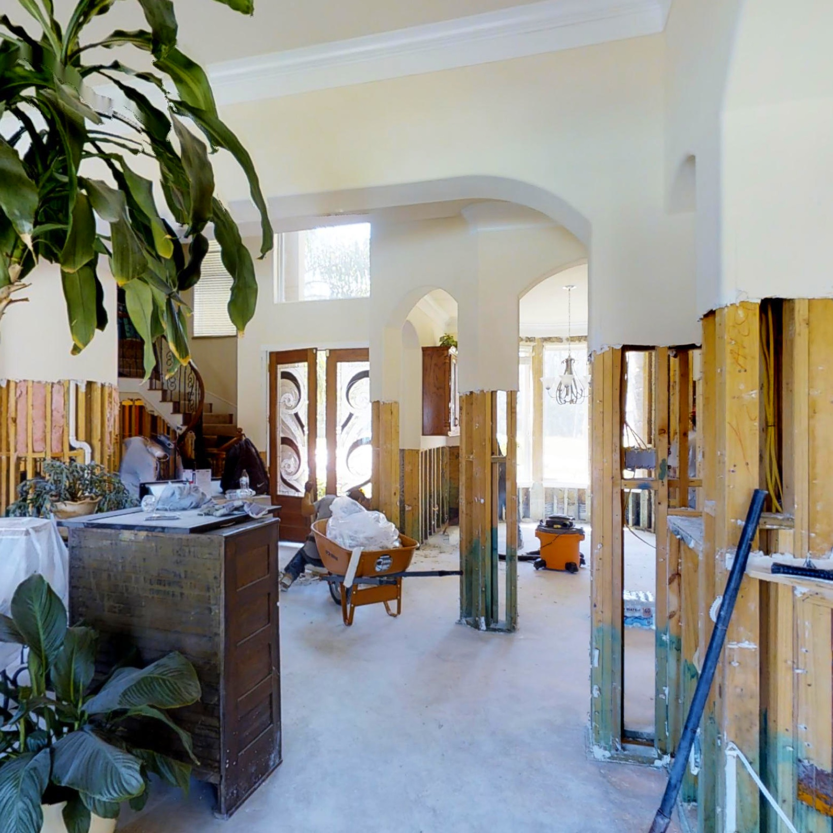 A half-finished living room, with house plants and construction equipment